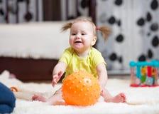 婴儿时期和人概念-在家使用与在地板上的球的愉快的婴孩 免版税库存图片