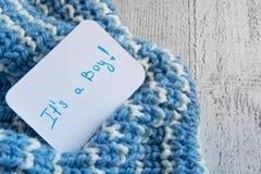 婴儿送礼会`它` s一男孩`、公告卡片在舒适羊毛蓝色毯子和空间文本的 在家庭的新的到来 库存图片