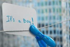 婴儿送礼会`它` s男孩` 垂悬在与蓝色晒衣夹的文本的导线和空间的简单的庆祝卡片 免版税库存图片