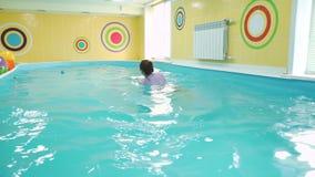婴孩下潜水中在游泳的教练帮助下  股票视频