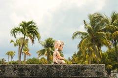 婴孩下跪在与高棕榈树defocused后面的一个坟墓的天使雕象特写镜头  免版税图库摄影