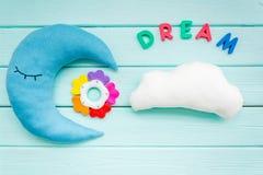 婴孩与月亮枕头、云彩、梦想拷贝和玩具的关心概念睡眠的新出生在薄荷的绿色背景顶视图 免版税图库摄影