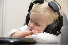 婴孩与耳机休眠 免版税库存照片