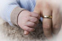 婴孩举行妈妈手指 免版税库存图片