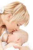 婴孩乳房提供的女孩她的亲吻母亲 免版税图库摄影
