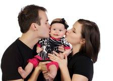 婴孩亲吻他们的年轻人的夫妇女孩 免版税库存照片
