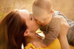 婴孩关闭亲吻温暖母亲的儿子 库存图片