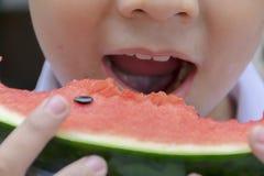 婴孩吃着与可口的西瓜 在酷暑期间,是 免版税库存图片
