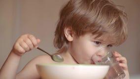 婴孩吃 在家吃早餐的逗人喜爱的孩子 甜矮小的笑的男婴画象有金发吃的 影视素材