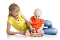 婴孩和他的妈妈演奏在白色隔绝的音乐玩具 库存图片