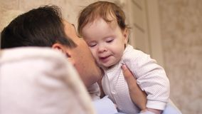 婴孩在他的在他的胃的父亲胸口说谎,并且父亲亲吻面颊的婴孩 慢动作, 影视素材