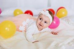 婴孩在床上说谎并且看与兴趣和微笑 女孩在一件美丽的礼服打扮和 免版税库存照片