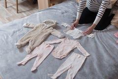 婴孩在床计划的` s衣裳,自然光上 免版税库存照片