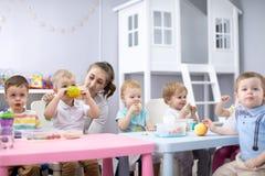婴孩在托儿所或托儿所的吃健康午餐 免版税库存图片