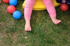婴孩在绿色草坪草的` s腿 免版税库存照片
