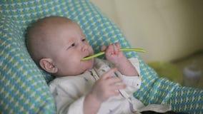 婴孩坐儿童` s椅子 妈妈第一次喂养有匙子的孩子 特写镜头 股票视频