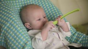 婴孩坐儿童` s椅子 母亲第一次喂养有匙子的孩子 特写镜头 影视素材