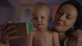 婴孩坐在与他的母亲的坏的和她显示他与她的电话关闭的动画片 股票视频