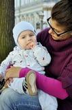 婴孩坐母亲膝部并且吃玉米球 库存图片