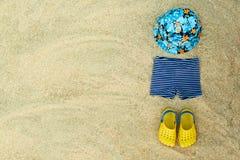 婴孩夏天海滩装,触发器,帽子,在沙子的短裤靠岸 库存图片