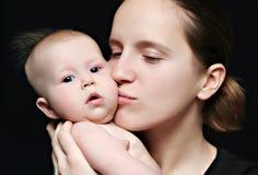 婴孩她亲吻的小母亲 库存照片