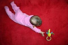 婴孩她的对玩具尝试的伸手可及的距离 库存照片