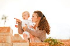 婴孩她的显示某事的感兴趣母亲 图库摄影