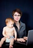 婴孩她的母亲工作 免版税库存照片