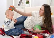 婴孩她的母亲演奏年轻人 免版税库存图片