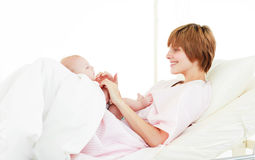婴孩她的演奏儿子的母亲 图库摄影