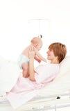 婴孩她的演奏儿子的母亲 免版税库存照片