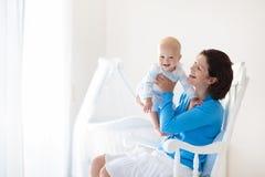 婴孩家庭母亲 妈妈和孩子在卧室 免版税库存照片