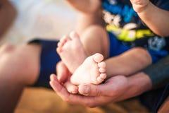 婴孩小的腿在父亲的手上 mindfull 图库摄影