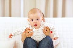 婴孩感兴趣舔母亲使用 图库摄影