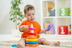 婴孩戏剧坐地板 幼儿园和幼儿园孩子的教育玩具 小男孩修造金字塔玩具在 库存图片