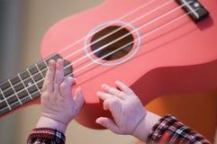婴孩手指弹吉他 尤克里里琴串和苦恼 免版税图库摄影