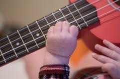 婴孩手指弹吉他 尤克里里琴串和苦恼 免版税库存图片