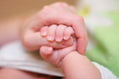 婴孩手指现有量暂挂母亲 库存照片