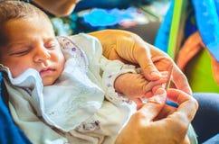 婴孩指甲锉切开了新出生屑子的钉子避免抓 图库摄影