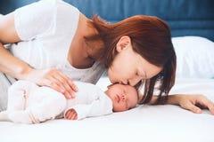 婴孩新出生她亲吻的母亲 免版税图库摄影