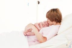 婴孩新出生她亲吻的母亲 免版税库存图片