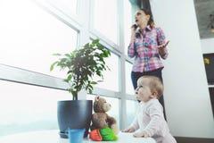 婴孩是未看管的 当妇女在电话时谈话,她的孩子在地板上爬行和被使用 免版税库存照片