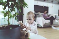 婴孩是未看管的 当妇女在电话时谈话,她的孩子在地板上爬行和被使用 库存图片