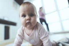 婴孩是未看管的 当妇女在电话时谈话,她的孩子在地板上爬行和被使用 库存照片