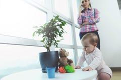 婴孩是未看管的 当妇女在电话时谈话,她的孩子在地板上爬行和被使用 图库摄影