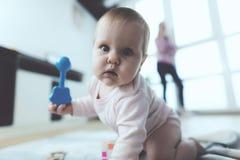 婴孩是未看管的 当妇女在电话时谈话,她的孩子在地板上爬行和被使用 免版税图库摄影