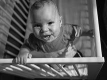婴孩有小儿床的乐趣 库存图片