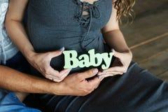 婴孩标识牌在手上怀孕 免版税库存照片