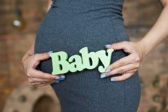 婴孩标识牌在未来怀孕的母亲的手上 免版税库存照片