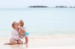 婴孩海滩女孩她亲吻的母亲 免版税库存照片